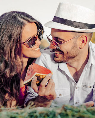 Happy Couple in Relationship eating watermelon on grass