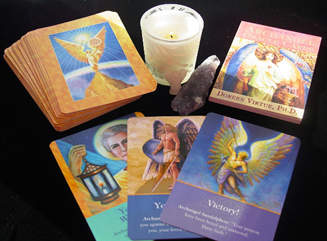 Selection of Angel Cards beside a crystal and candle