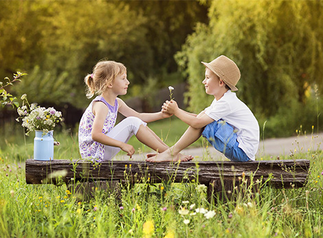 Young girl and boy sitting on a log facing each other smiling showing Inner Child Healing