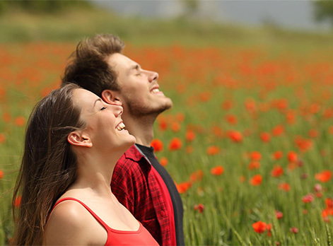 Happy couple smiling in a field of flowers after having Wellness Coaching